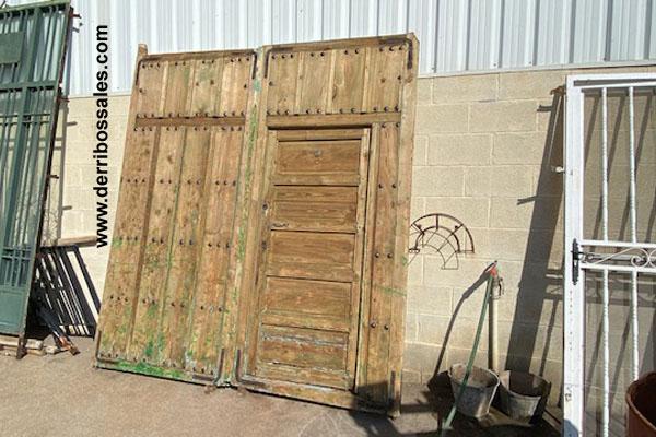 Portón antiguo de madera, con clavos. Compuesto de 2 hojas y puerta de paso. Medidas: 250 x 234 cm. Grosor de 7 cm.