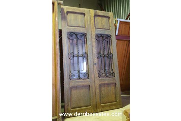 Puerta de madera de 2 hojas, con reja.